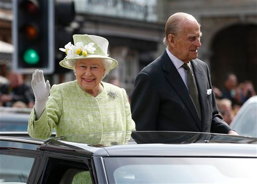 Britain's Queen Elizabeth II waves to the crowds as she rides with Prince Phillip in a open top car to celebrates her 90th birthday in Windsor, England, Thursday, April, 21, 2016.