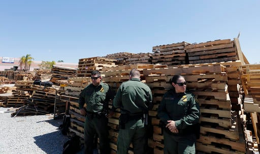 U.S. Border Patrol agents look on during a news conference in a lot alongside the border with Mexico Wednesday, April 20, 2016, in San Diego. A nearly half-mile-long tunnel leading from Mexico to San Diego was discovered and more than a ton of cocaine and