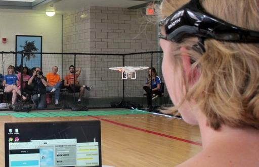 In this April 16, 2016 photo. a University of Florida student uses a brain-controlled interface headset to fly a drone during a mind-controlled drone race in Gainesville, Fla.