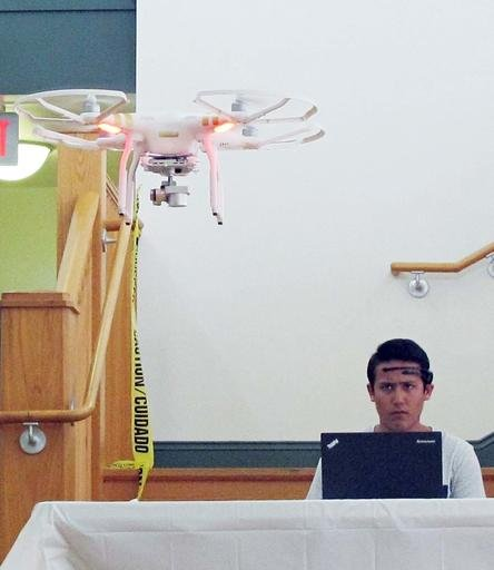 In this photo taken April 16, 2016, University of Florida sophomore Michael Lakin, 19, uses a brain-controlled interface headset to fly a drone during a mind-controlled drone race in Gainesville, Fla.