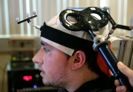 In this photo from April 13, 2016 Richard Tursi, 19, undergoes therapy that uses a brain-controlled technology to help improve his motor functions at the Miami Project to Cure Paralysis at the University of Miami Miller School of Medicine in Miami.