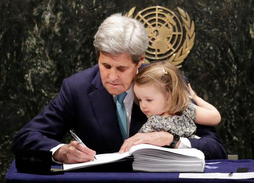 U.S. Secretary of State John Kerry holds his granddaughter Isabel Dobbs-Higginson as he signs the Paris Agreement on climate change, Friday, April 22, 2016 at U.N. headquarters.