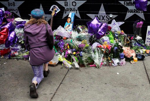 A woman kneels by the memorial at First Avenue Friday, April 22, 2016, in Minneapolis where Prince often performed. The pop super star died Thursday at the age of 57. (AP Photo/Jim Mone)