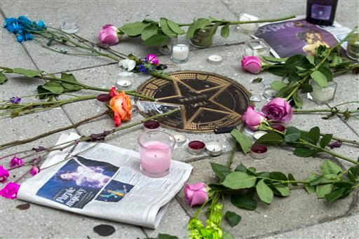 Flower are placed around musician Prince's star in a makeshift memorial on the sidewalk outside of the Warner Theatre in Washington, Friday, April 22, 2016.