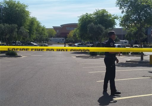 Chandler police spokesman Seth Tyler stands behind crime tape at the scene of a police involved shooting at a Walmart store on Saturday, April 23, 2016 in Chandler, Ariz.