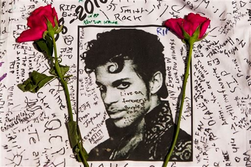 Flowers lay on a T-shirt signed by fans of singer Prince at a makeshift memorial place created outside Apollo Theater in New York, Friday, April 22, 2016.