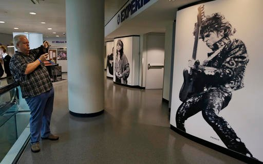 Miles Smith, from Houston, Texas, takes a picture of a mural of Prince at the Rock and Roll Hall of Fame and Museum, Friday, April 22, 2016, in Cleveland.