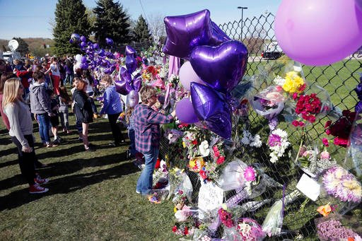 A memorial fence in memory of pop star Prince is lined with flowers and signs at Paisley Park Studios Friday, April 22, 2016 in Chanhassen, Minn.