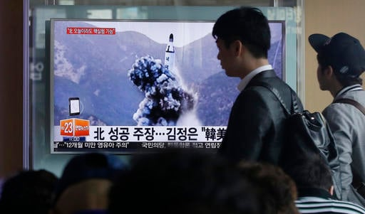People walk by a TV news program showing an image published Sunday in North Korea's Rodong Sinmun newspaper of North Korea's ballistic missile that the North claimed to have launched from underwater, at Seoul Railway station in Seoul, South Korea, Sunday,