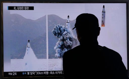 A South Korean man watches a TV news program showing images published Sunday in North Korea's Rodong Sinmun newspaper of North Korea's ballistic missile that the North claimed to have launched from underwater, at Seoul Railway station in Seoul, South Kore