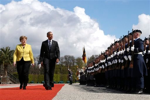 German Chancellor Angela Merkel, left, and U.S. President Barack Obama review the guard of honour at Herrenhausen Palace in Hannover, northern Germany, Sunday, April 24, 2016. Obama is on a two-day official visit to Germany. (AP Photo/Michael Sohn, pool)