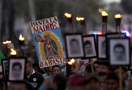 In this Dec. 26, 2015, file photo, relatives of the 43 missing students from the Isidro Burgos rural teachers' college march and hold pictures of their missing loved ones during a protest in Mexico City. Mexico's national human rights commission said Thu