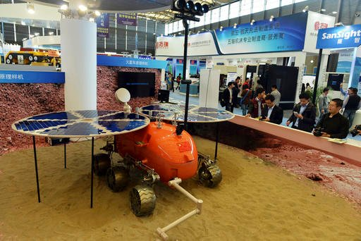 In thi Nov. 4, 2014, file photo, visitors to the 16th China International Industry Fair (CIIF) look at a prototype of what a Chinese Mars rover would look like in Shanghai, China. Head of the China National Space Administration Xu Dazhe said Friday, April