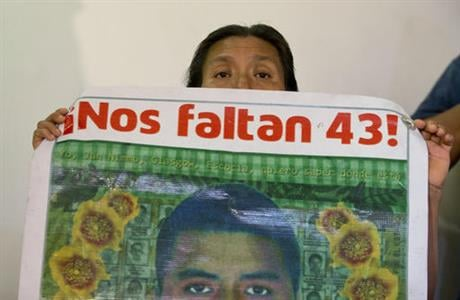 """A woman holds up a photograph of a missing student with a caption reading """"We are missing 43,"""" during a press conference by the parents of missing teachers college students in response to a report issued Sunday by the Inter-American Commission on Human Ri"""