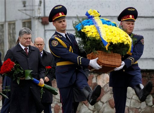 Ukraine's President Petro Poroshenko, left, carries flowers as he arrives at a monument to the victims of the Chernobyl tragedy.