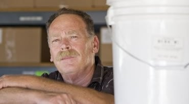 Jim Wiseman leans on a bin of wheat in front of food stores in his garage in La Jolla, Calif. Thursday, May, 7, 2009. Six months ago, Jim Wiseman didn't even have a spare nutrition bar in his cabinet. Now, the 54-year-old businessman and father of five ha