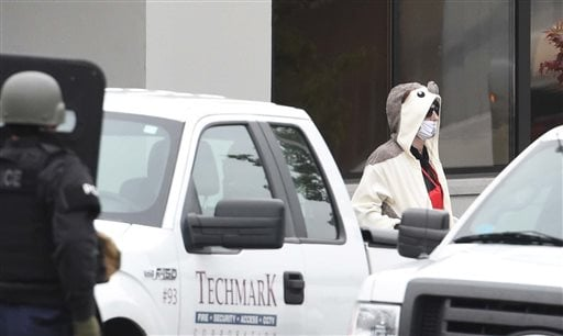 A man wearing a full animal costume and surgical mask walks out of a TV station in Baltimore, Thursday, April 28, 2016. Baltimore police say a department sniper shot the man, who police say walked into a TV station displaying what appeared to be an explos