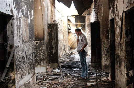 In this Oct. 16, 2015, file photo, an employee of Doctors Without Borders walks inside the charred remains of the organization's hospital after it was hit by a U.S. airstrike in Kunduz, Afghanistan.