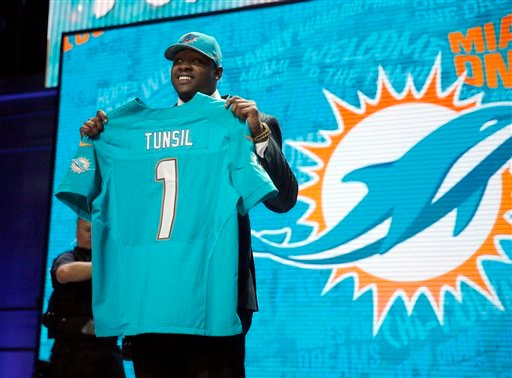 Mississippi's Laremy Tunsil poses for photos after being selected by the Miami Dolphins as the 13th pick in the first round of the 2016 NFL football draft, Thursday, April 28, 2016, in Chicago.