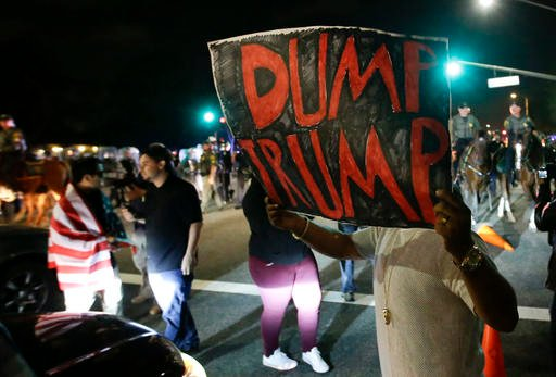 Protestors pushed off the street by law enforcement after a rally for Republican presidential candidate Donald Trump, Thursday, April 28, 2016 in Costa Mesa, Calif. (AP Photo/Chris Carlson)