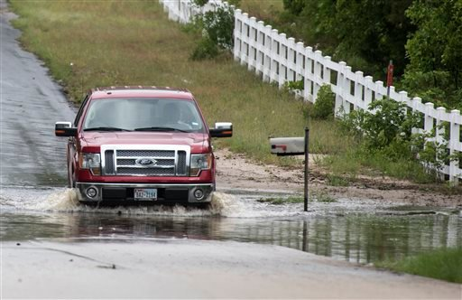 A man drives through floodwaters near the Ozarka Wood County Bottling Plant in Hawkins, Texas, Saturday, April 30, 2016.