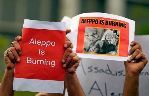 Protesters hold up placards during a protest in front of the United Nations Headquarters in Beirut, Lebanon, Sunday, May 1, 2016, against Syrian President Bashar Assad's military operations in areas held by insurgents around the country, mostly in the nor
