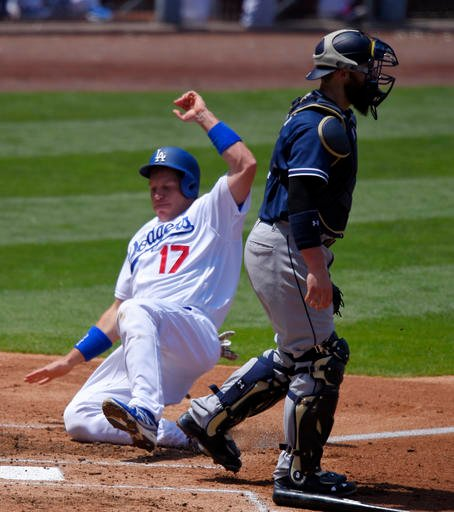 Los Angeles Dodgers' A.J. Ellis, left, scores on a single by Clayton Kershaw as San Diego Padres catcher Derek Norris stands by during the third inning of a baseball game, Sunday, May 1, 2016, in Los Angeles. (AP Photo/Mark J. Terrill)