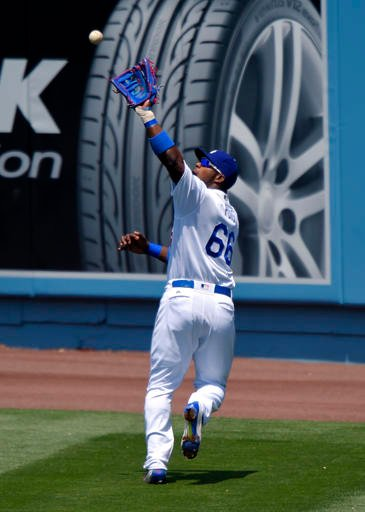 Los Angeles Dodgers right fielder Yasiel Puig catches a ball hit by San Diego Padres' Alexei Ramirez during the second inning of a baseball game, Sunday, May 1, 2016, in Los Angeles. (AP Photo/Mark J. Terrill)