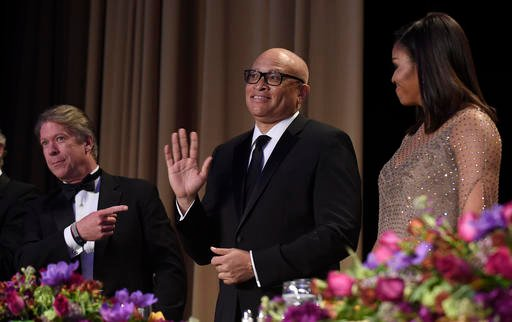 Larry Wilmore, guest host from Comedy Central, center, waves as he is introduced at the annual White House Correspondents' Association dinner at the Washington Hilton, in Washington.