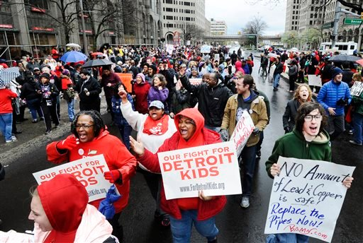 Members of the Detroit Federation of Teachers march down Grand Blvd., during a rally in front of the Detroit Public Schools offices in Detroit, Monday, May 2, 2016.