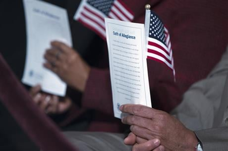 """Participants hold the """"Oath of Allegiance"""" and American flags during a naturalization ceremony attended by President Barack Obama at the National Archives in Washington. (AP Photo/Evan Vucci, File)"""