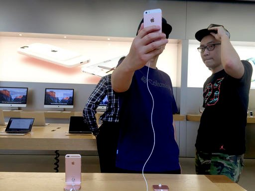 Shoppers try out an iPhone at a Apple retails store in Beijing, China, Wednesday, May 4, 2016.