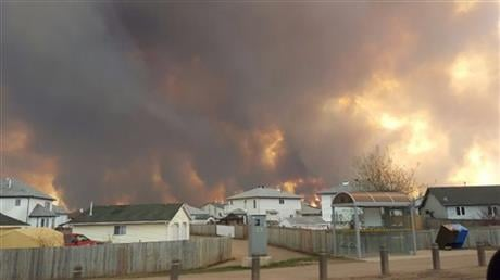 The entire population of the Canadian oil sands city of Fort McMurray, has been ordered to evacuate as a wildfire whipped by winds engulfed homes and sent ash raining down on residents. (Mary Anne Sexsmith-Segato/The Canadian Press via AP)