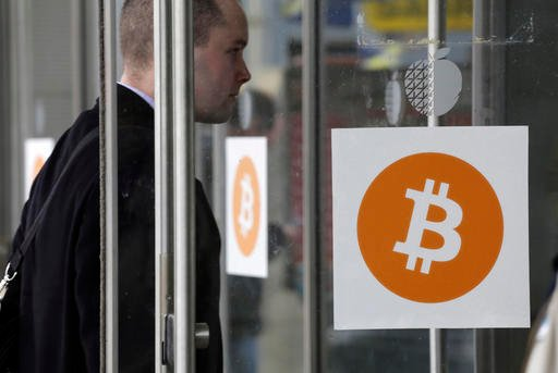In this Monday, April 7, 2014, file photo, a man enters the Inside Bitcoins conference and trade show, in New York. Australian entrepreneur Craig Wright, the man who came forward on Monday, May 2, 2016, as bitcoin's founder, is backtracking from his claim