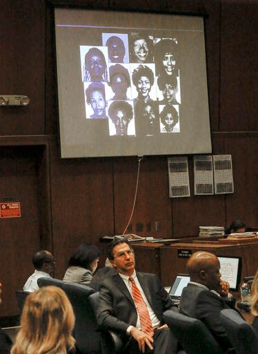 In this May 2, 2016 file photo, a montage of photos of alleged victims is projected on a screen in the courtroom during the during closing arguments in the serial murder trial of Lonnie Franklin Jr., seated at far left, in Los Angeles Superior Court. Fran