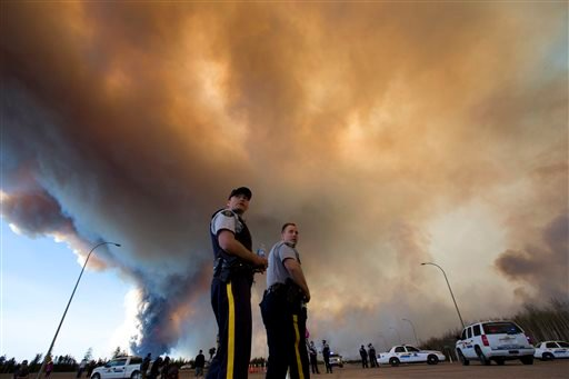 Police officers direct traffic under a cloud of smoke from a wildfire in Fort McMurray, Alberta, Canada on Friday, May 6, 2016.