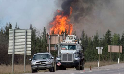 Flames from a wildfire billow into the sky south of Fort McMurray, Alberta, on Highway 63 on Saturday, May 7, 2016.