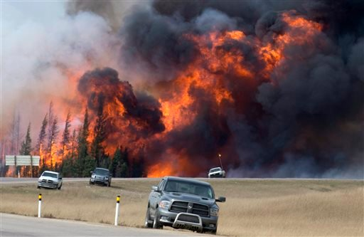 A wildfire burns south of Fort McMurray, Alberta, near Highway 63 on Saturday, May 7, 2016. Canadian officials hoped to complete the mass evacuation of work camps north of Alberta's main oil sands city of Fort McMurray on Saturday, fearing the growing wil