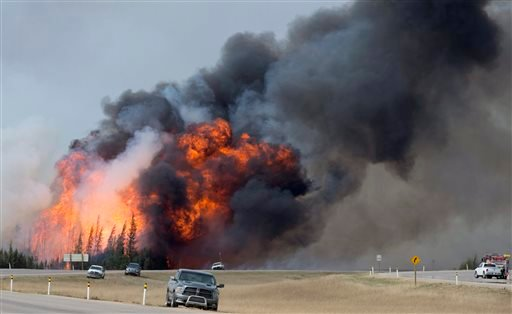 Flames from a wildfire billow into the sky south of Fort McMurray, Alberta, on Highway 63 on Saturday, May 7, 2016. Canadian officials hoped to complete the mass evacuation of work camps north of Alberta's main oil sands city of Fort McMurray on Saturday,