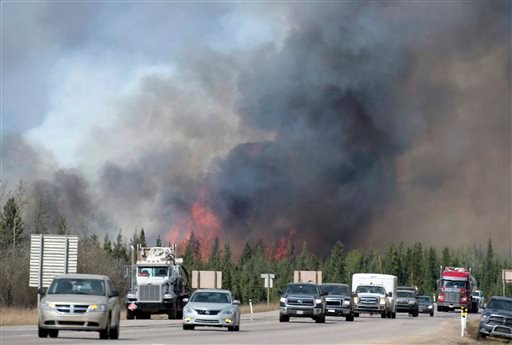 A convoy of cars and trucks pass a wildfire as they are evacuated from Fort McMurray, Alberta, on Highway 63 south of the city on Saturday, May 7, 2016. Canadian officials hoped to complete the mass evacuation of work camps north of Alberta's main oil san