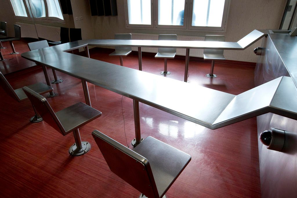Surveillance cameras, right, are mounted underneath a metal table with chairs bolted to the floor where addicts can inhale heroin fumes in a clinic in Amsterdam, Netherlands, Tuesday, April 12, 2016. Such facilities have operated for years in Vancouver, B