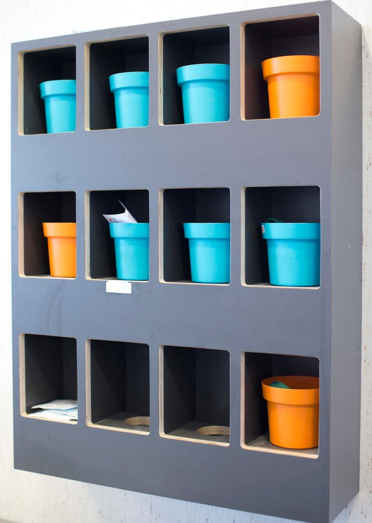 A rack holds colored plastic cups with their owners' names taped onto them in a room where addicts inject heroin in a clinic in Amsterdam, Netherlands, Tuesday, April 12, 2016. The cups contain an tourniquet used by the addicts to help find a vein. (AP Ph