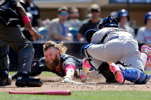 San Diego Padres' Andrew Cashner, center, is tagged out at home by New York Mets catcher Kevin Plawecki, right, during the fifth inning of a baseball game Sunday, May 8, 2016, in San Diego. (AP Photo/Gregory Bull)