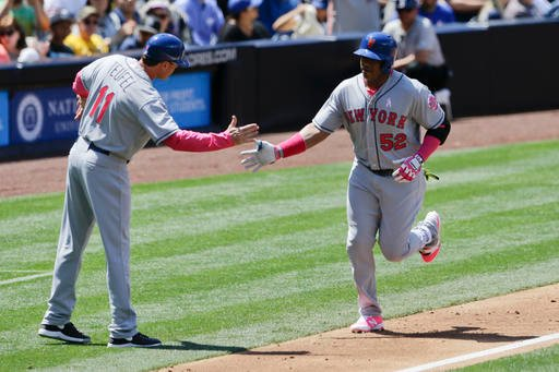 New York Mets' Yoenis Cespedes, right, greets third base coach Tim Teufel after hitting a home run during the third inning of a baseball game against the San Diego Padres, Sunday, May 8, 2016, in San Diego. (AP Photo/Gregory Bull)