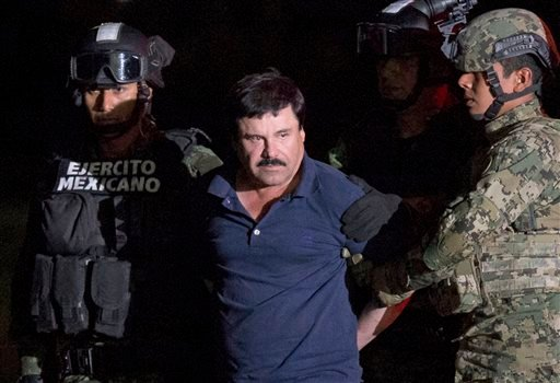 "In this Jan. 8, 2016 file photo, Mexican drug lord Joaquin ""El Chapo"" Guzman is escorted by army soldiers to a waiting helicopter, at a federal hangar in Mexico City, after he was recaptured from breaking out of a maximum security prison in Mexico. The Hi"