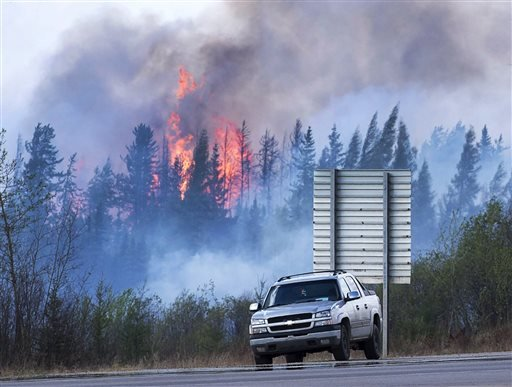Flames flare up from hotspots from a wildfire along a highway to Fort McMurray, Alberta, Canada, Sunday, May 8, 2016. (Ryan Remiorz/The Canadian Press via AP)
