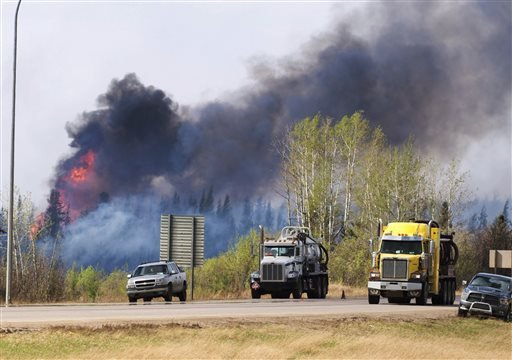 Flames flare up from hotspots along the highway to Fort McMurray, Canada, Sunday, May 8, 2016. (Ryan Remiorz/The Canadian Press via AP)