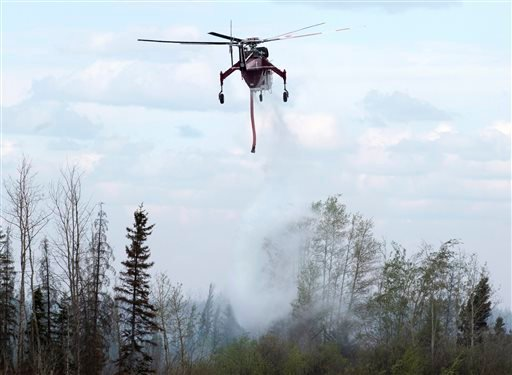 A helicopter drops water on hot spots along the highway to Fort McMurray, Canada, Sunday, May 8, 2016. (Ryan Remiorz/The Canadian Press via AP)