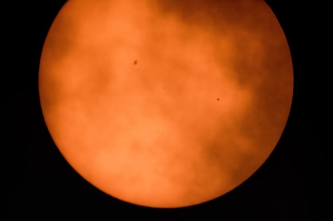This is a viewer-submitted photo of the transit of Mercury taken Monday morning, using a telescope and solar filter as clouds rolled in. Mercury is on the right. Other dark spots are sunspots. (Monday, May 9, 2016. Photo courtesy: J. Miller.)