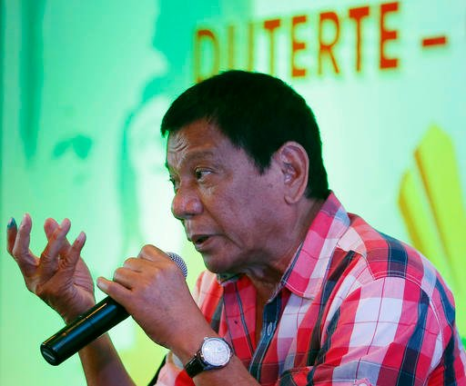 Front-running presidential candidate Mayor Rodrigo Duterte gestures during a news conference shortly after voting in a polling precinct.